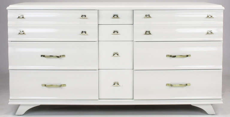 White lacquer ten-drawer dresser by Kling Furniture of Mayville, NY. Centre four drawers are recessed, adding emphasis to the six fluted front drawers to either side. Lightly toned brass over zinc drop U and scalloped flat bar pulls. Restored with