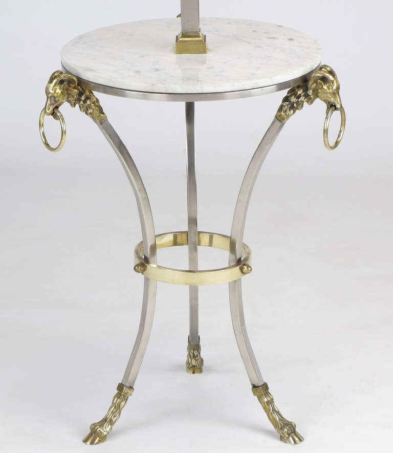 Neoclassical Italian nickel and brass floor lamp with Carrara marble tabletop. Tripodal curved legs with brass hoof feet and ram heads with ringed ornaments. Double socket cluster with adjustable height finial. 