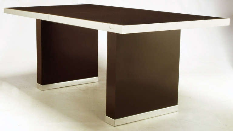 Clean lined elegance from iconic French designer, Pierre Cardin. Dark chocolate laminate over wood with chrome banding covering the edge of the table top and pedestal bases. Very well cared for it's entire life. Comes with two 18