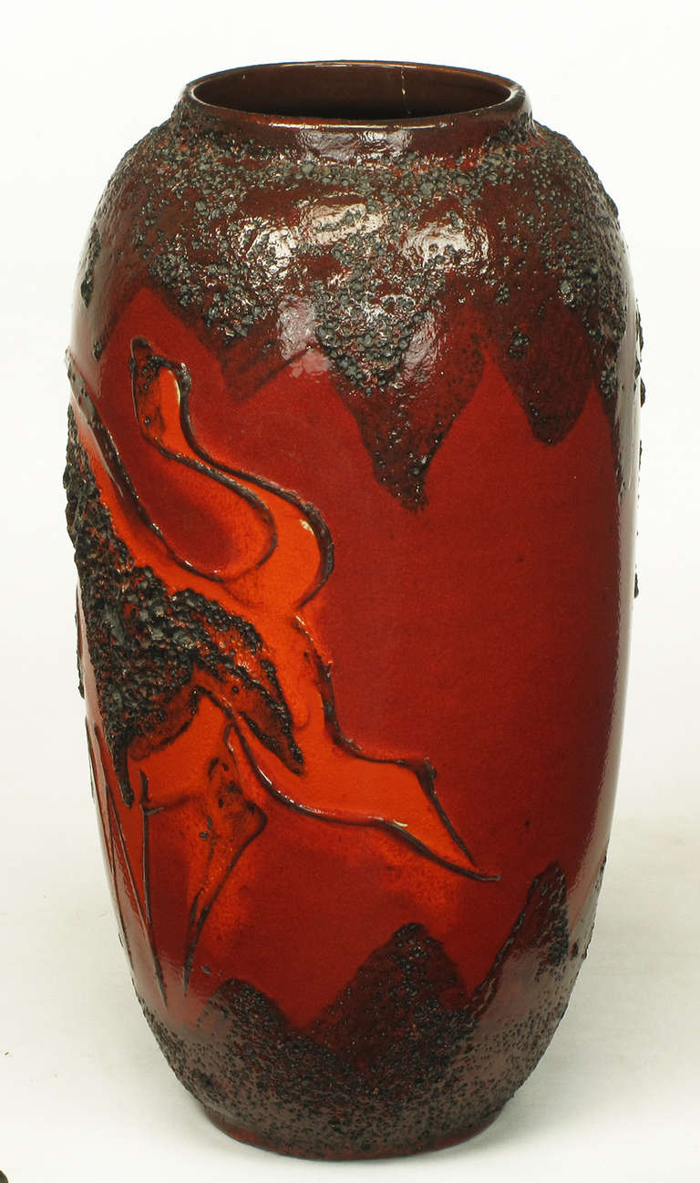 "West German Scheurich Keramic tall vase in a red and black lava glaze finish with black and orange outlined relief glazed bull and black relief lava glaze volcanos. Single volcano to the back of the vase is erupting, showing the ""lava"" to the top of"