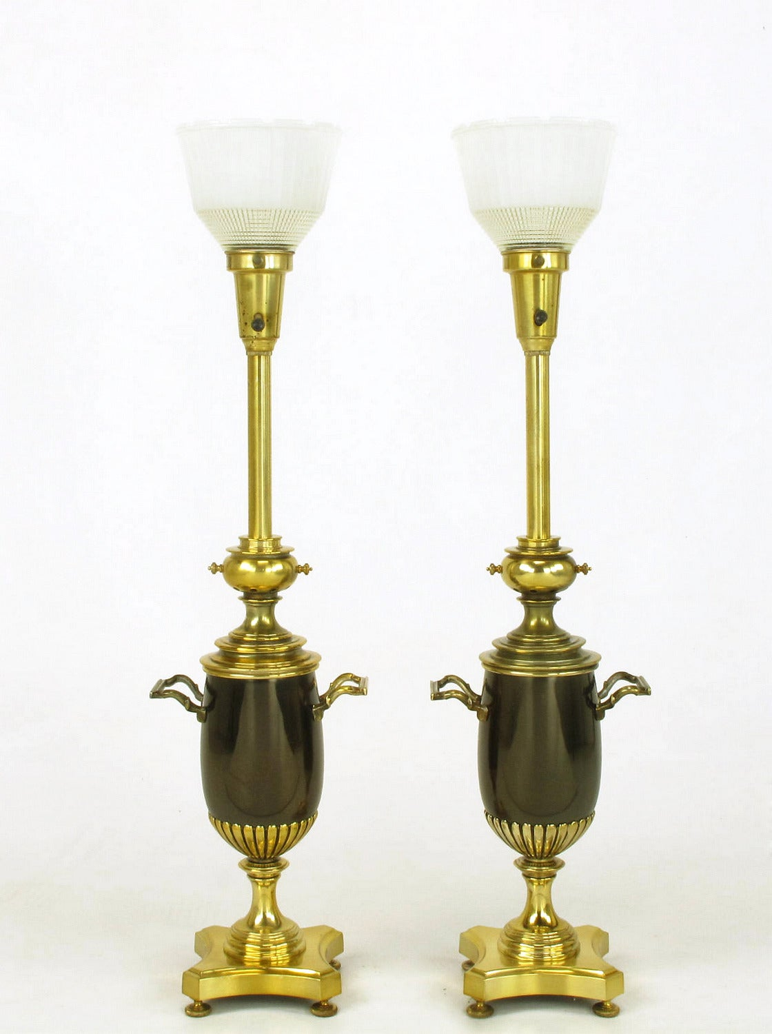 Pair of brass toned silver and bronze urn form table lamps. Urn bodies are bronze with a pair of handles. Reverse quatrefoil footed base, flanged riser, reeded cup, spacers and stem all finished in brass toned lacquer over silver. Manufactured by