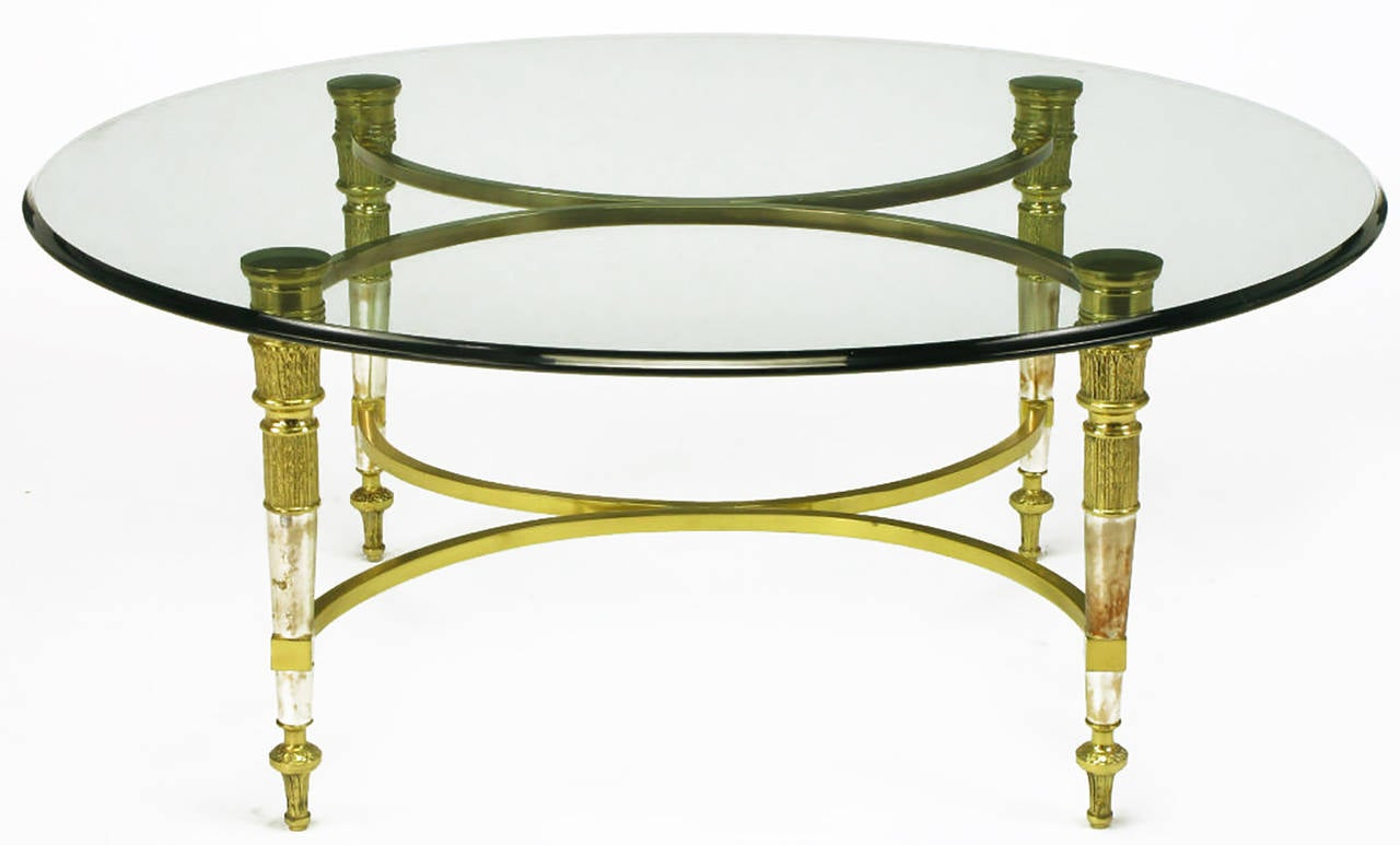 Solid brass and aged nickel Empire style coffee table in the manner of Labarge, with segmented pillar legs and rounded X-stretcher supports to the bottom and top. A quarter inch thick round glass top with an ogee beveled edge.