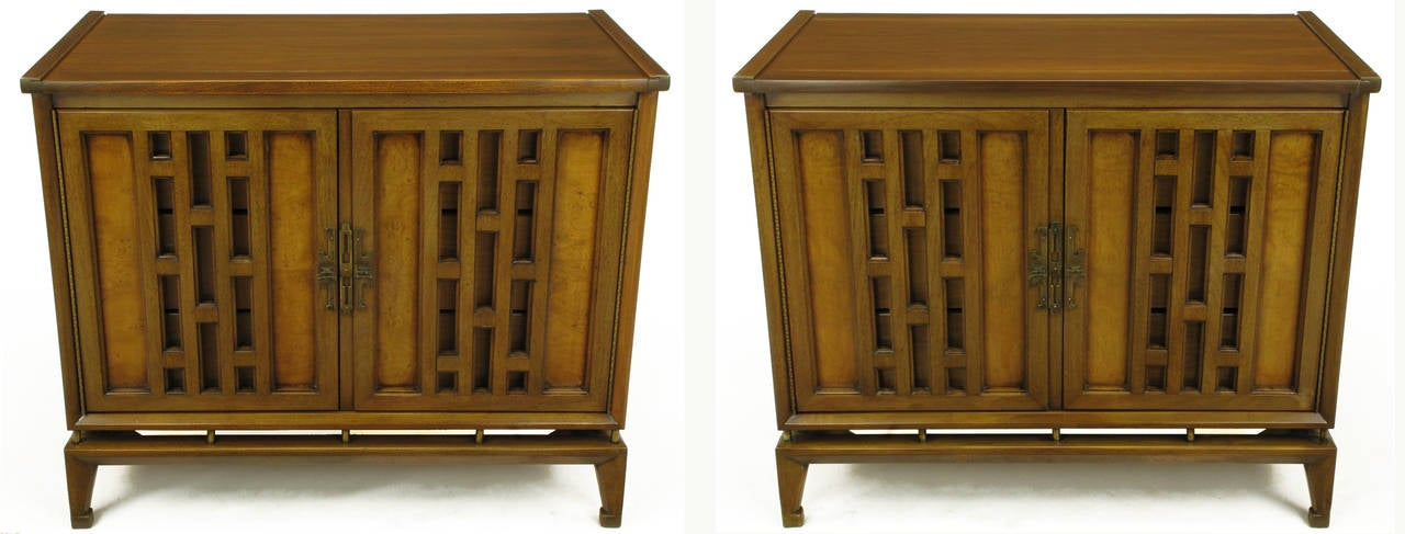 Pair of walnut cabinets with floating cabinets and open fretted doors by White Furniture. Each cabinet door has open fret work panels and burled wood recessed panels with Asian inspired, patinated brass pulls and escutcheons. Doors open to reveal