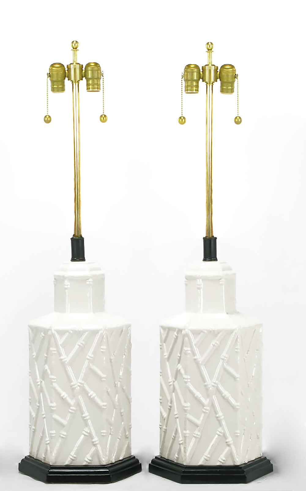Pair of hexagonal shaped white ceramic bodied table lamps, with a patterned bamboo relief. Black lacquered and stepped hexagonal wood base and black lacquered metal and brass stems with double socket clusters. Sold sans shades.