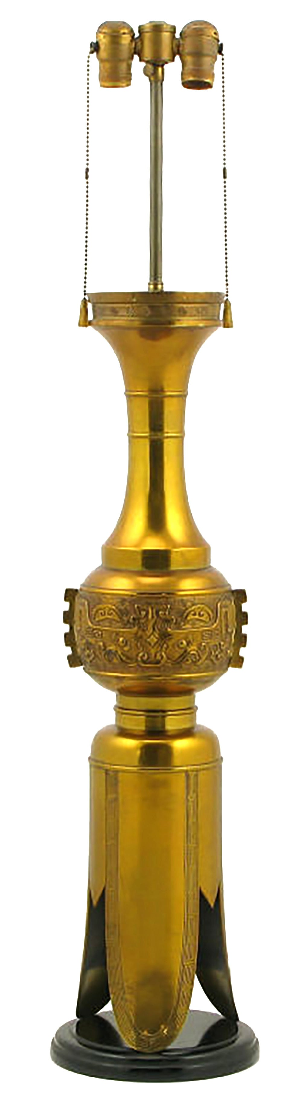 Large and unexpected, Chinese inspired table lamp in incised brass with Greek key detailing. Double socket illumination with pull chains and ebonized carved wood plinth base. Sold sans shade.