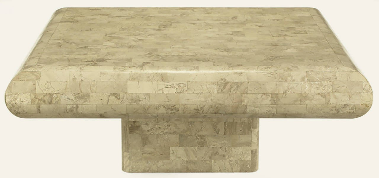 Tessellated fossil stone coffee table with radiused edges and recessed pedestal base. Made in the same factory as similar designs by Karl Springer and Maitland Smith.