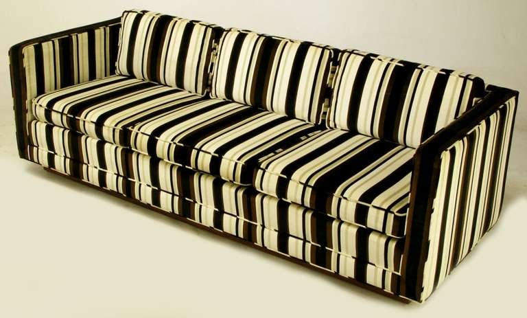 Three-seat even arm tuxedo sofa in striped brown, black, taupe and white velvet upholstery. Loose seat and back cushions walnut platform base.