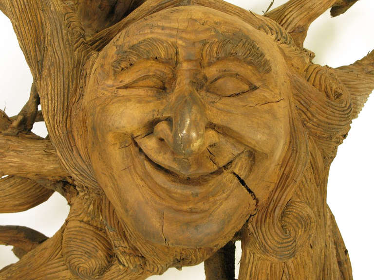 Substantial 72 inch x 78 inch hand-carved Folk Art wall sculpture. Comprised of a large tree root with attached additional roots and carved centre smiling face. Every square inch is carved with striations as well as the centre face.