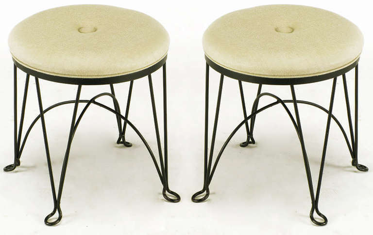 Pair of round black wrought iron stools in the style of Salterini. Four V-Form legs with open tear drop feet. Domed X stretchers. Reupholstered in heavy taupe linen with large center buttons.