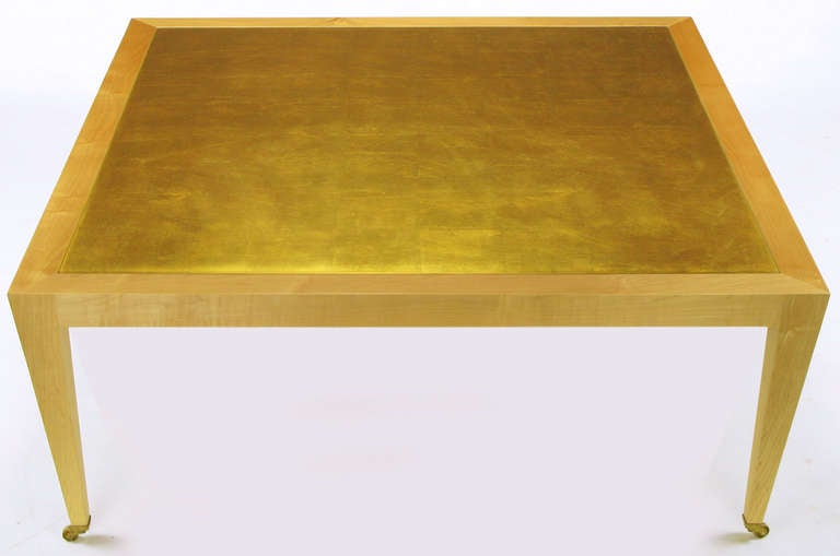 Donghia square form maple framed coffee table with brass caster and gold leafed inset wood top.