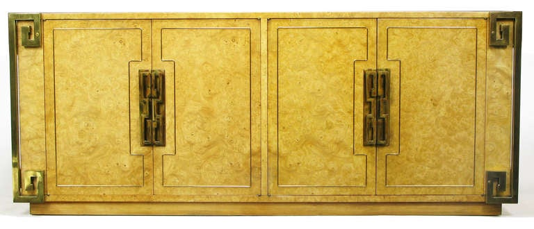 Natural amboyna burl case, with four brass-welted doors accented by heavy brass pulls and backing plates. Doors open to reveal five drawers and a single shelf. Four corners are adorned with heavy brass Greek key detail. Early cloth label.