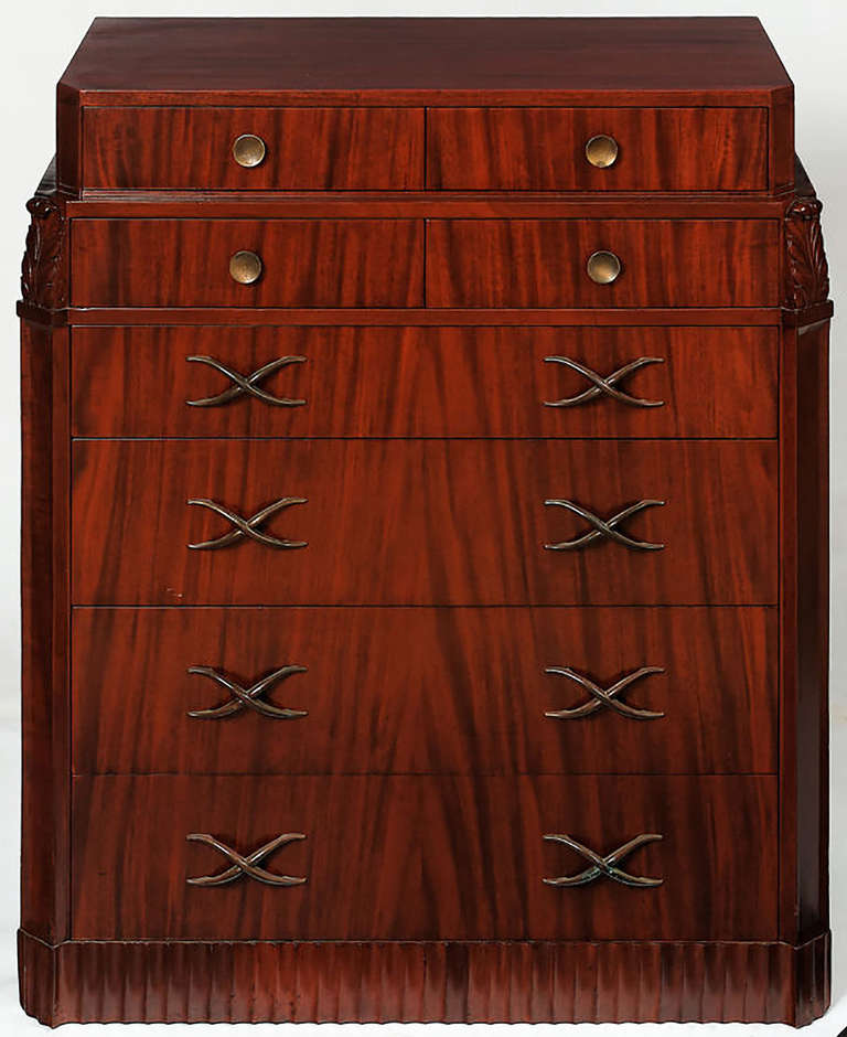 Striking Art Deco/moderne design tall chest with ziggurat top and canted front corners. The fluted base and acanthus leaf ornamentation are accented by large X-form bronze drawer pulls that retain a subtle patina. Attributed to Lorin Jackson.