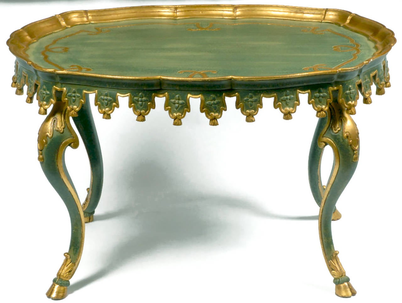 Shaped like a squared-off oval, this table is carved of wood, including tassel ornamentation and hoof feet crested with acanthus leaf trim. Painted a lovely teal blue-green, with an ivory over glaze, it is accented by gilded trim. Marked