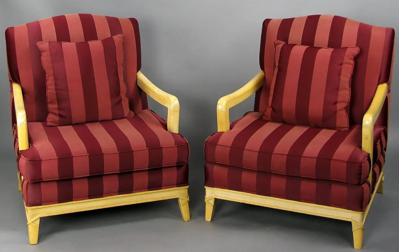 Rustic and refined pair of camel back open-arm lounge chairs. Carved wood frames with a distressed lacquer finish. All four legs have wood carved to simulate rawhide banding. Upholstered in a two-tone oxblood silk stripe fabric.