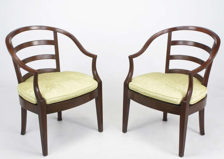 Pair of barrel and slat back curvacious mahogany arm chairs with down filled cushions covered in the original silk moire. Loose cushions also have a second inconspicuous loose seat cushion, recessed into the solid wood seat; a Bert England hallmark.