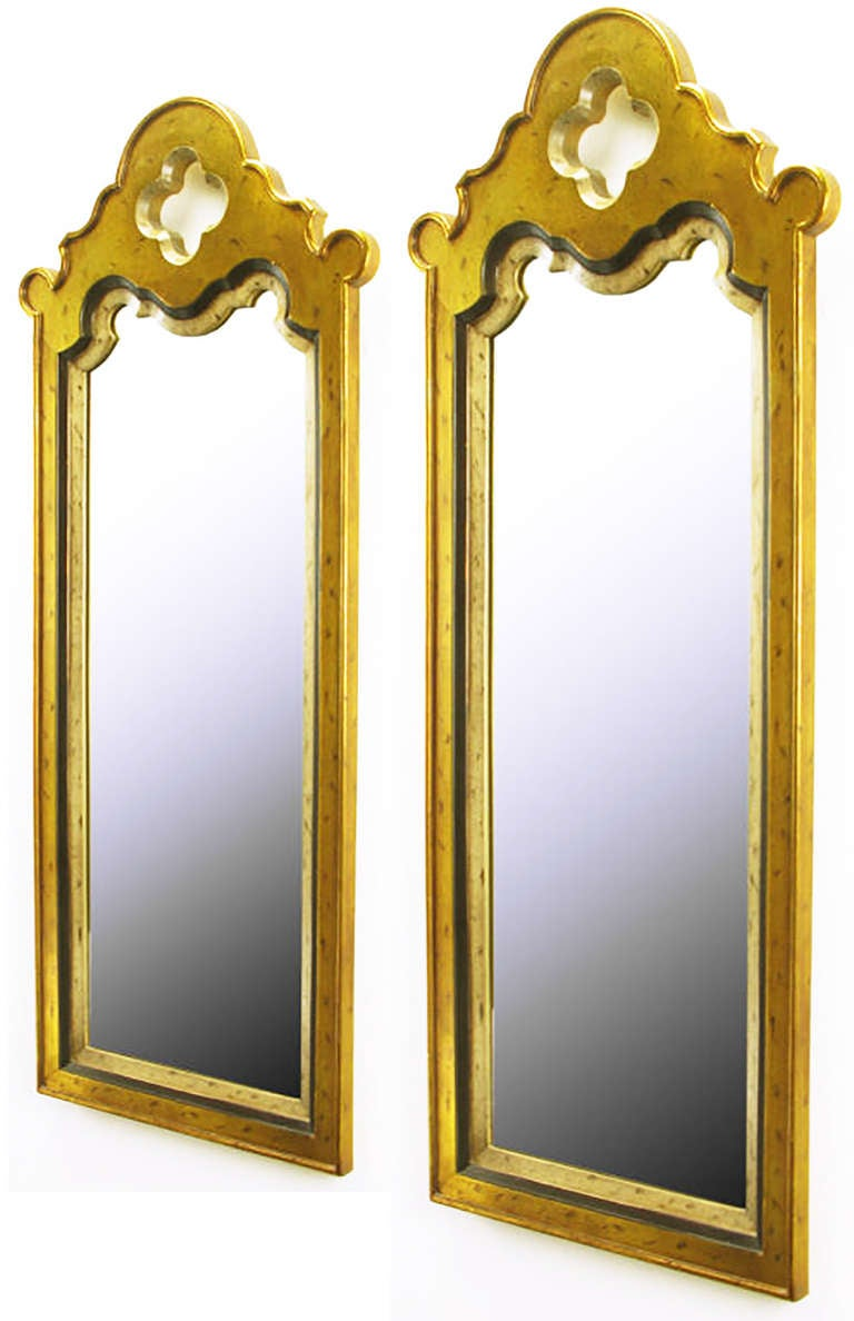 Pair of cast resin Moorish design mirrors with patinated gold and silver leaf finish. Tall and narrow with inset frame and quatrefoil top opening.
