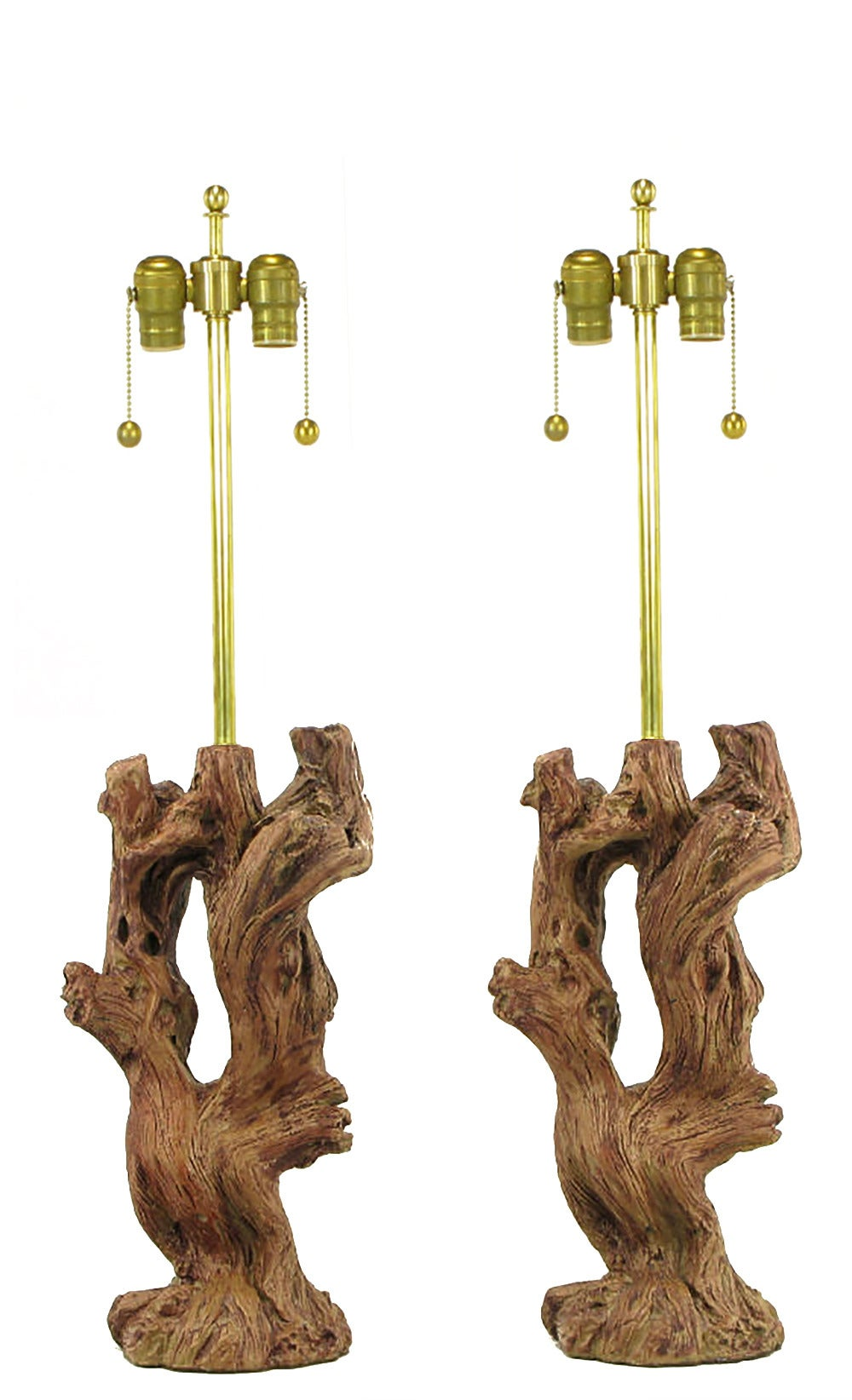 Pair of ceramic faux bois driftwood bodied table lamps with beautifully authentic glazing. Brass stem and double socket cluster, sold sans shades.