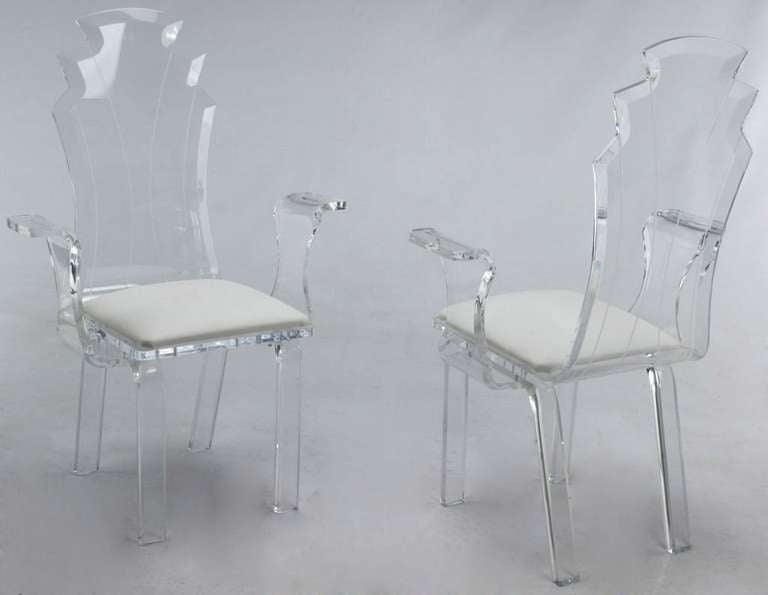 Elegant set of six acrylic dining chairs with beveled and etched scalloped backs. Thick seats are done in a high quality white vinyl, and the arm chairs have sinuous arms. Similar to designs by Leon Frost.
