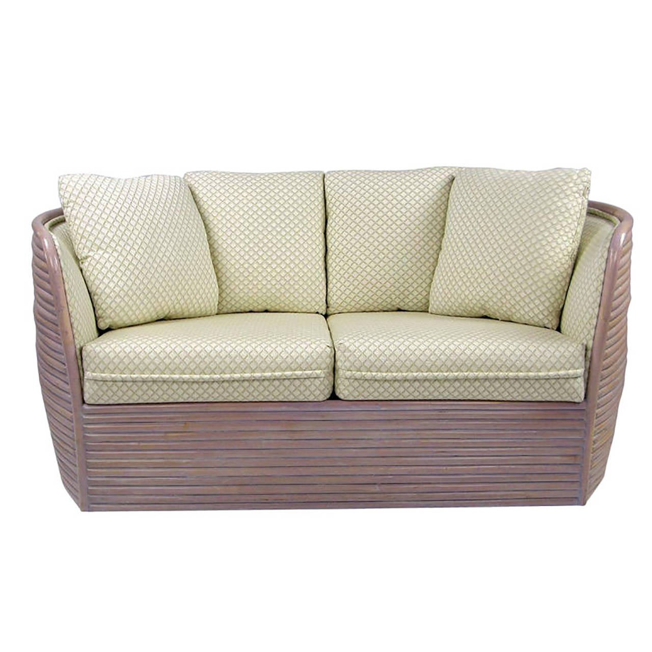 Baker takes some design cues from the 1970s with this bombe rattan settee. Reeded frame that bows out in the middle is washed in white primer and lavender lacquer. Two-seat cushions, four back cushions, all upholstered in a vintage cream, taupe and