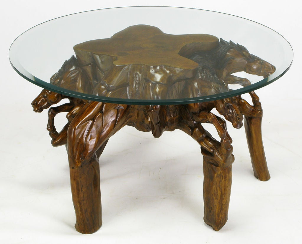Glass top coffee table with carved wood stallion base at