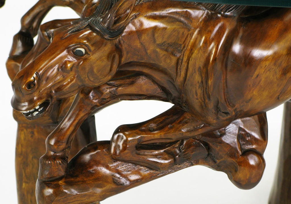 Glass top coffee table with carved wood stallion base image