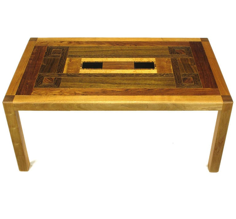 Exotic wood specimen inlaid marquetry top Parsons style coffee table. Each wood specimen is separated by a very thin boarder of beech wood. Solid birch wood inlaid with ebony, walnut, Macassar ebony, rosewood, teak and maple. Signed on bottom and