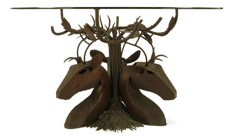 Singular artisan glass top dining table. Comprised of a trio of stylized deer busts, with antlers intertwined with tree branches. Hand welded and torch cut steel busts, antlers, and tree limbs with trunk and roots. Would also make an excellent