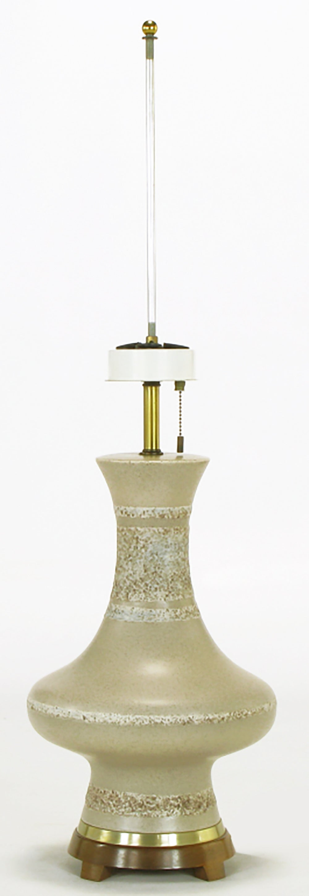 Modernist urn form table lamp with a heathered glaze pottery body, footed wood base and brass spacer. Brass stem with a three socket up light mechanism that was a Lightolier hallmark. Possibly a late Gerald Thurston or early David Cressey design.