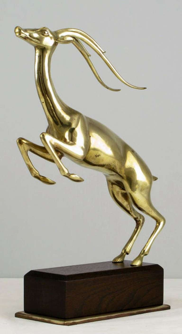 Expertly cast and finished brass leaping gazelle sculpture mounted on a brass plinth based walnut pedestal.