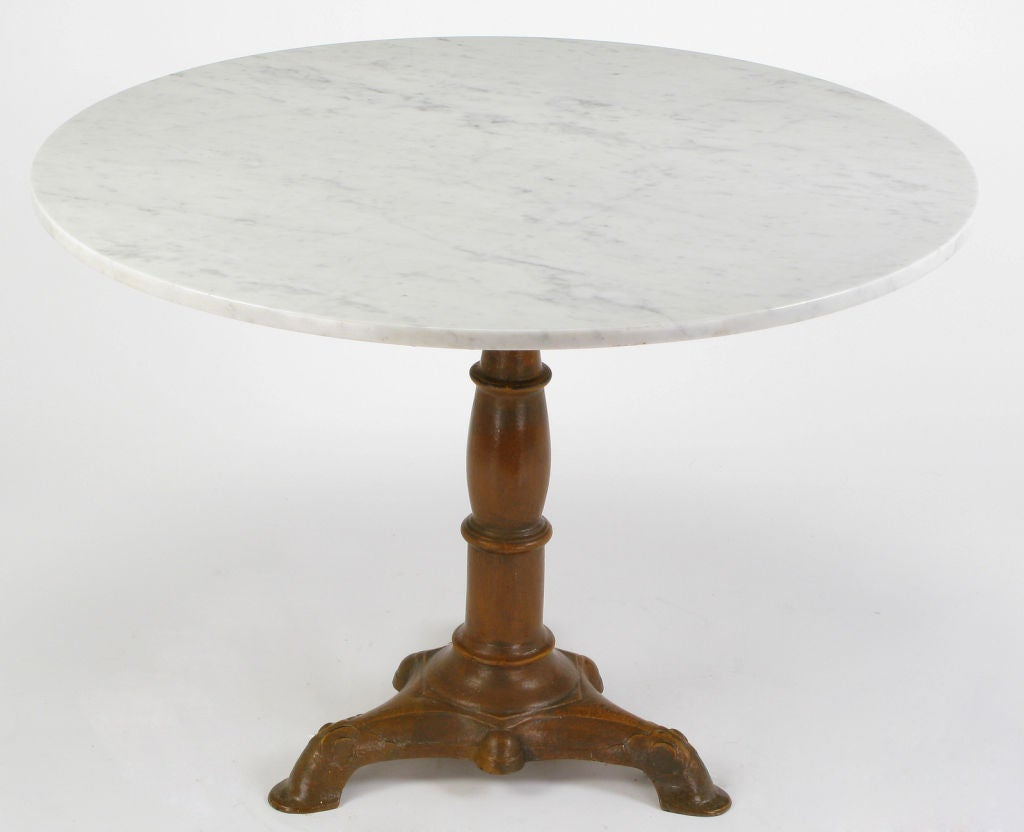 round carrera marble and cast iron pedestal dining table