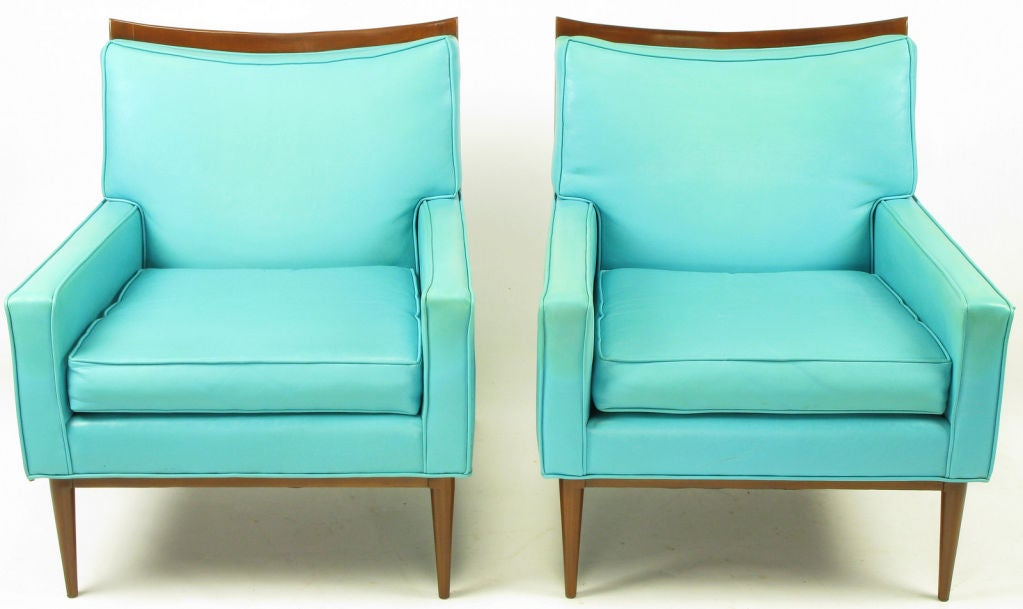 Pair of Paul McCobb for Directional lounge chairs in fine quality turquoise vinyl upholstery, with walnut frames restored to excellent condition. Similar in styling to the Widdicomb club chairs by T.H. Robsjohn-Gibbings.