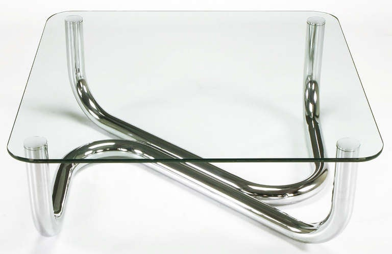 """Sinuous chrome tube and glass coffee table in the spirit of Paul Tuttle's """"anaconda"""" coffee table for Strässle International. Two conjoining large diameter chrome tubes in a snake like design with chrome caps and a radiuses corner 1/2"""" thick glass"""