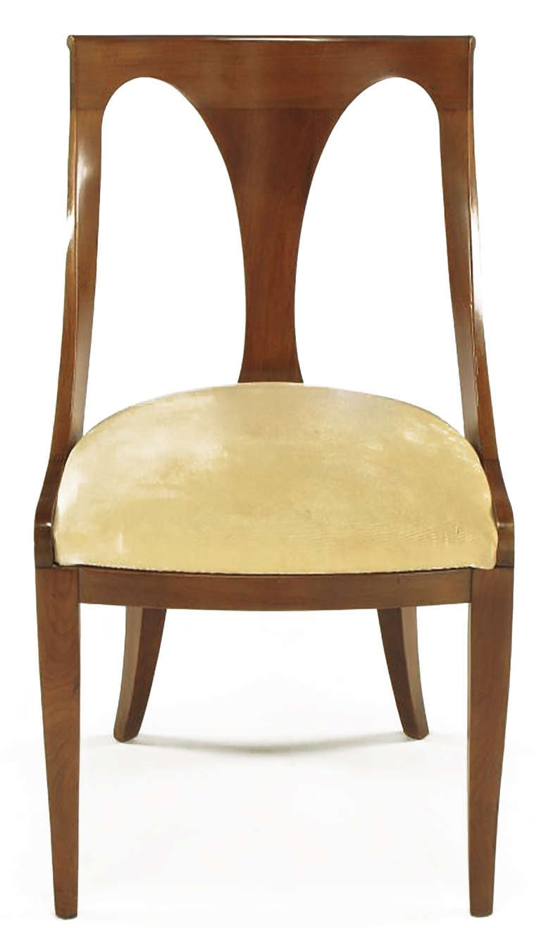 Set of four walnut and cream velvet Italian Regency scooped back dining chairs by Kindel, circa 1950s. Uncommon lower curvature detail to the front tapered saber legs.