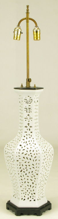 Reticulated blanc de chine table lamp in hexagonal vase form, with Asian character design in the neck. Black lacquered wood base and metal cap with brass stem and dual socket illumination. Sold sans shade.