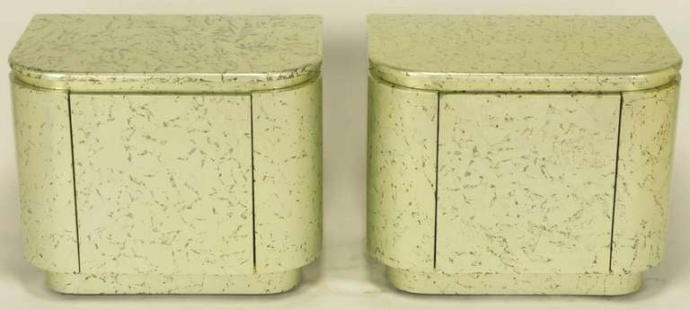 Pair of textured gilt radius edge single door cabinets with single shelf. Sophisticated silver leaf underfinish with flecked black glazing, sealed under clear champagne gold lacquer. Single shelf interior lacquered in matte black. Originally