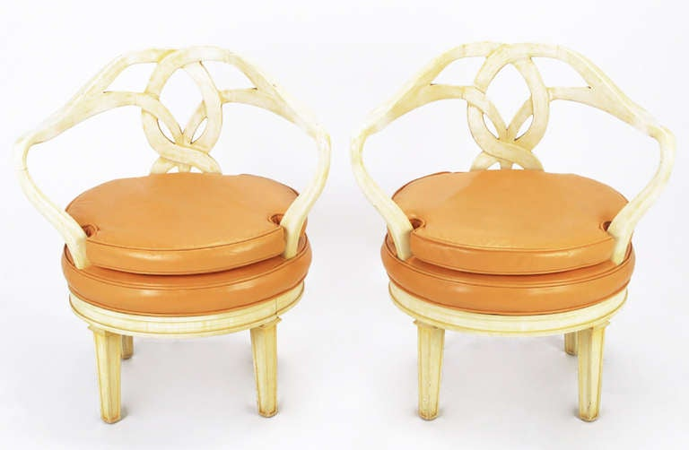 Striking and sculptural pair of Italian Empire style swiveling armchairs. Round seats and sinuous arms that intertwine to form the back. Frames are finished in a cream lacquer under a saffron glaze. Seats are upholstered in pumpkin color leather.