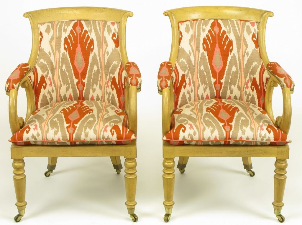 Pair of Regency armchairs with factory distressed wood frames and cotton/silk blend ikat print upholstery in white, taupe grey, persimmon and rose.  By Interior Crafts of Chicago, IL. Scrolled and padded arms with curved upholstered backs and loose