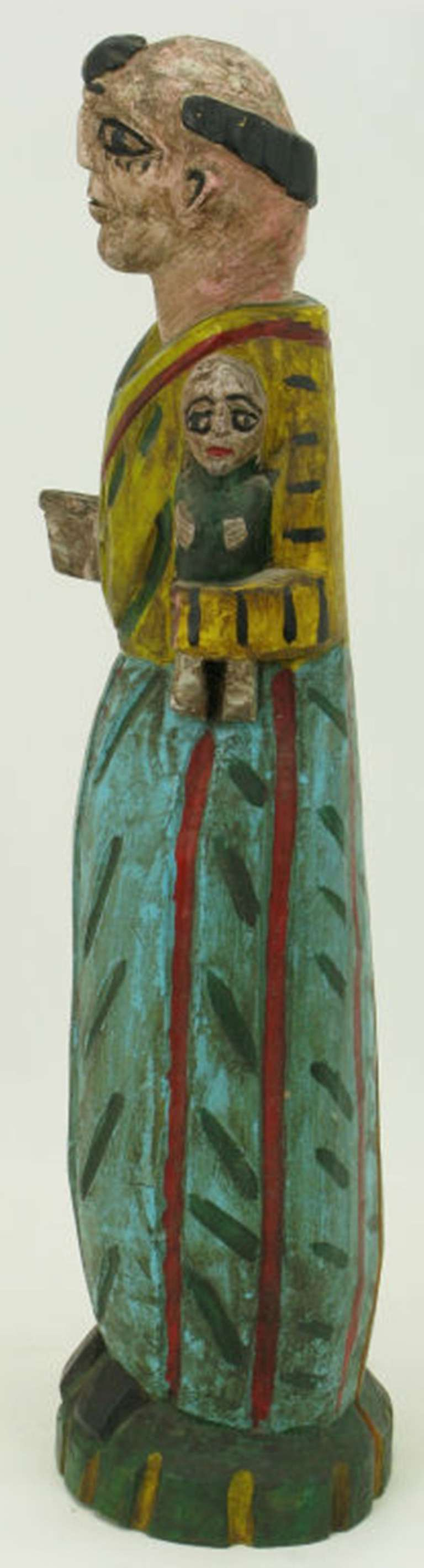 Hand carved and painted santo with child, possibly John The Baptist. The vivid polychrome colors and primitive wood carving make for a striking folk art piece.