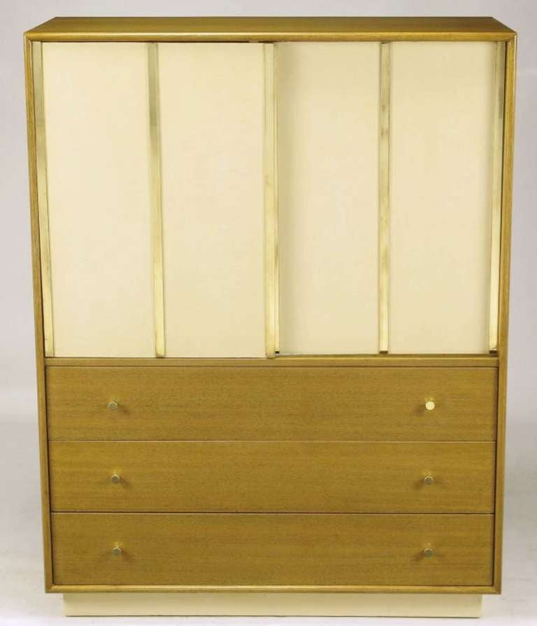 Harvey Probber bleached mahogany tall dresser or gentleman's chest, with ivory leather-clad sliding doors that feature brass flat bar appointments. Behind the doors there are four drawers and three sliding shelves. Three lower drawers open via