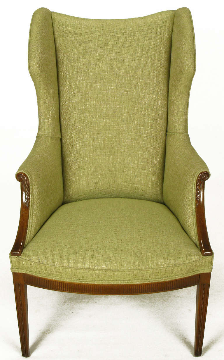 Inspired design with Italian flair, this fully restored sculptural wing chair has exposed and carved mahogany elements with saber back legs, fluted apron with recessed and beaded front legs. New taupe/sage silk and linen upholstery.