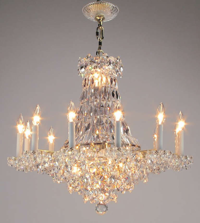 Beautiful Art Deco revival crystal chandelier with twelve lights/arms. Half basket lower section is reflected in a mirrored disc that separates the top and bottom and reflects both. Two links of chain currently, however adding chain to lengthen the