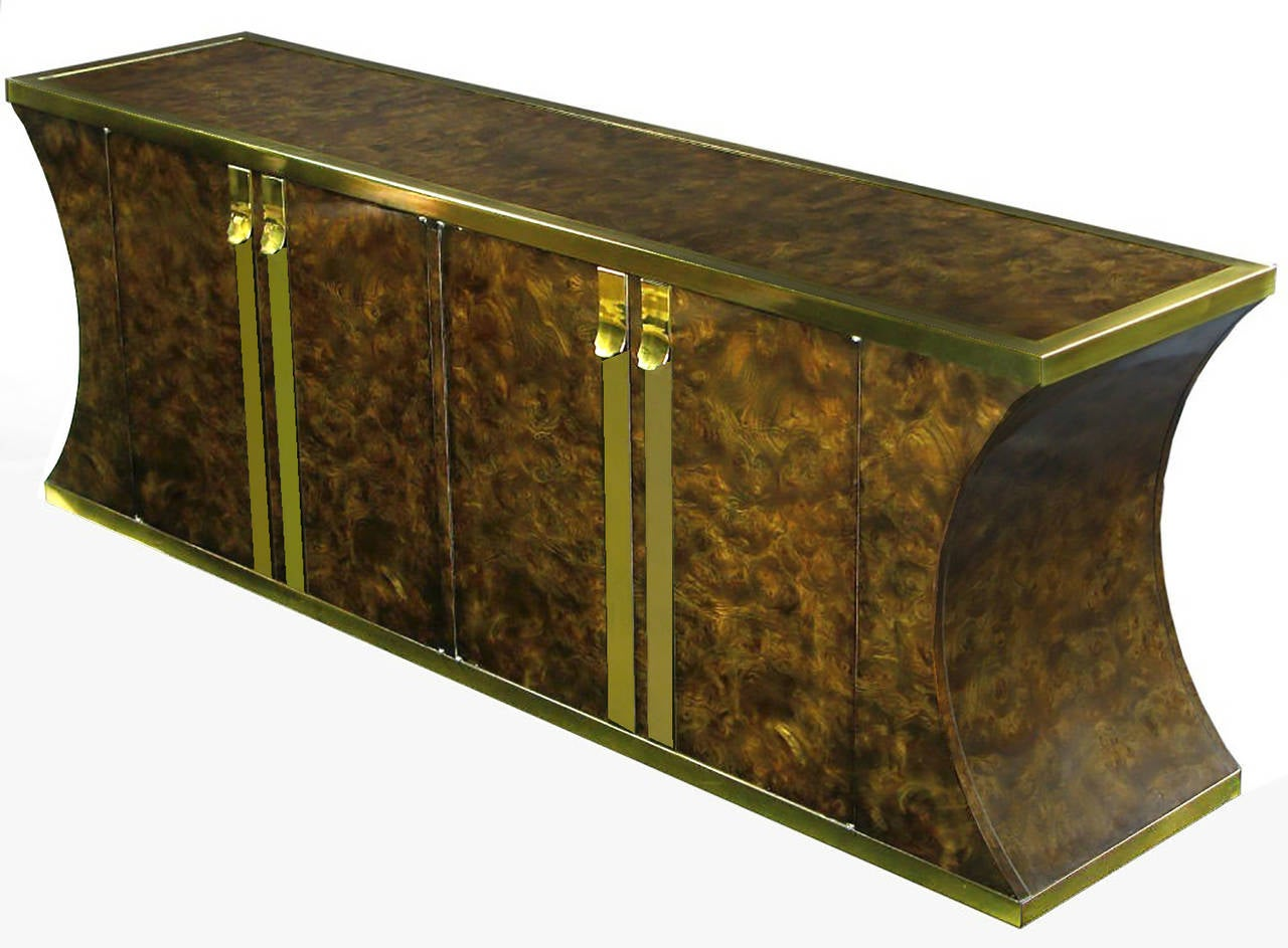 Mastercraft sideboard clad in vibrant Amboyna burl veneer, with heavy brass appointments. It is quite striking, with its inverted curve ends. Four drawers on one side, and shelf storage on the other.