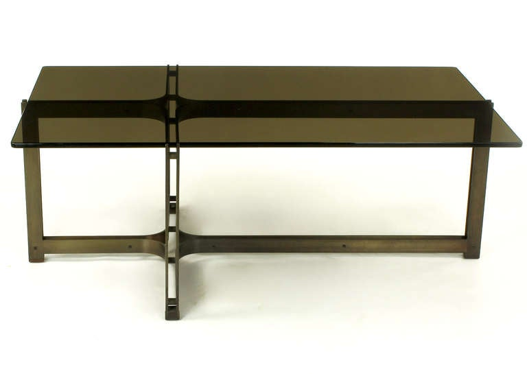 Interconnected brushed bronze architectural coffee table base with bronze spacers, rosewood caps and feet, and smoked glass top by Tom Lopinsky for Dunbar. The top fits securely into reveal of each end.  Lopinski designed for Dunbar from 1965