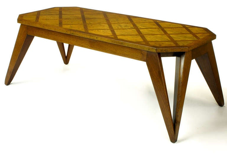 Excellent parquetry inlaid top coffee table with canted corners and raked open triangular legs. Studio piece with subtle refinement. Beautiful figured and bleached walnut top with mahogany cross hatch inlay. Unexpected open triangular legs a