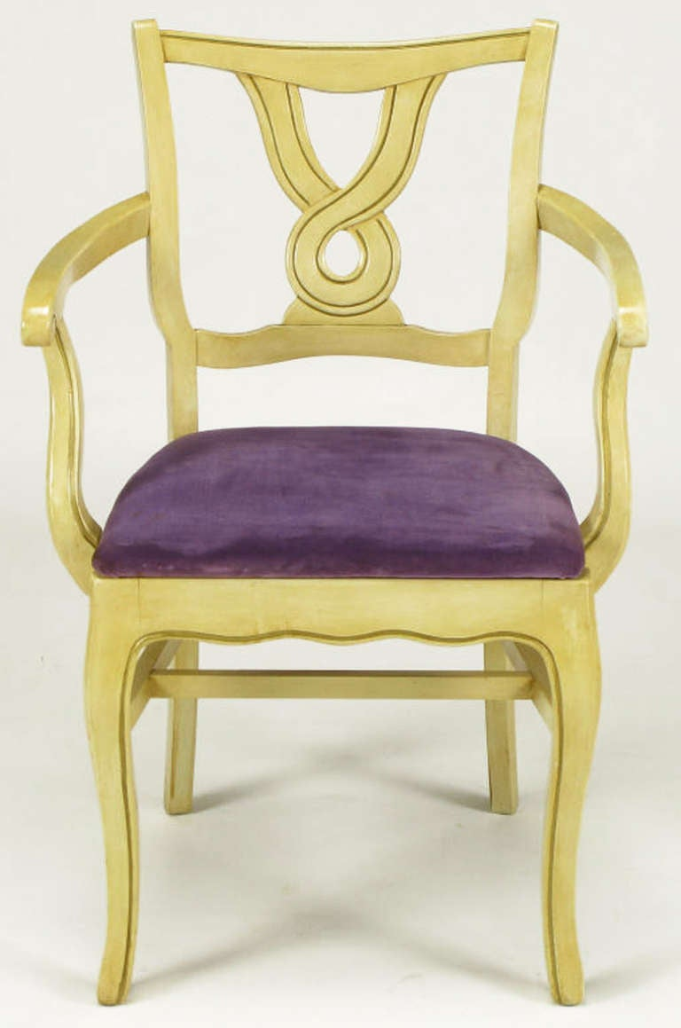 Uncommon set of six regency style dining armchairs with ivory glazed and parcel gilt carved wood frames with amethyst velvet seats. Cabriole front legs with scalloped aprons and high stretchers. Backs are a unique crossed ribbon open circle carving.