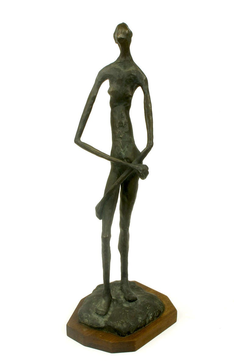 Bronze sculpture in the manner of Alberto Giacometti. Female nude with arms crossed mounted on walnut plinth. Signed Billing.