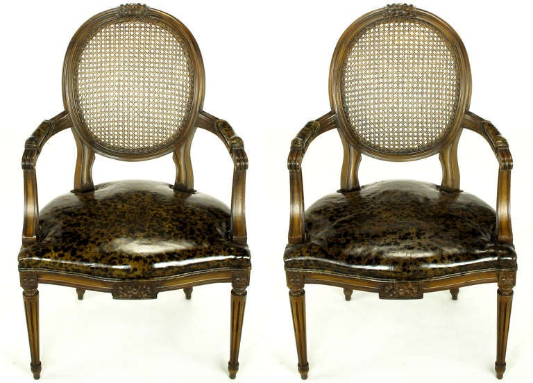Excellent pair of Louis XVI style chairs with tortoise shell leather seats and arm pads. Hand-carved mahogany and fruit wood frames with rosettes and fluted legs. Sturdy pair of great looking, early 20th century reproductions that are faithful to