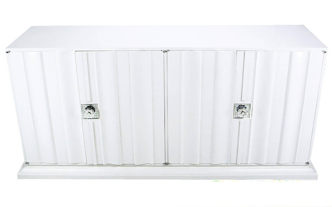 Pair of white lacquer sideboard cabinets in the manner of Tommi Parzinger. Linen fold relief to the doors with large nickel-plated pulls with square cross hatch escutcheons and stepped plinth three sided base. Custom made for a Miami Florida home in