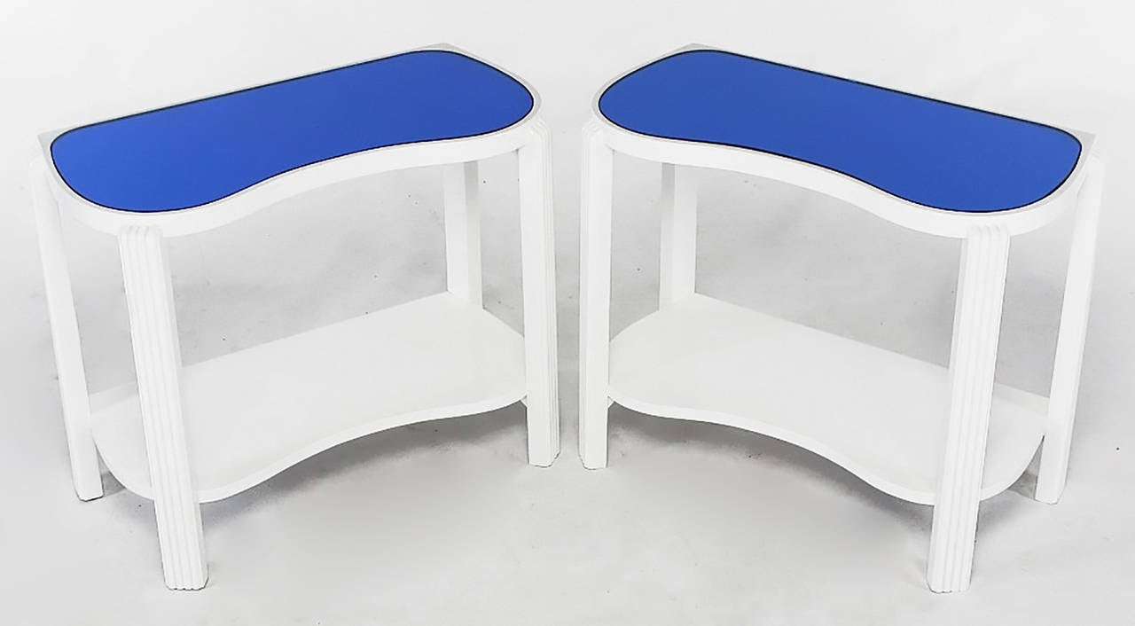 Uncommon pair of American Art Deco end tables finished in white gloss lacquer with blue tinted mirrored tops. Sinuous top and lower tier supported by reeded and canted legs.