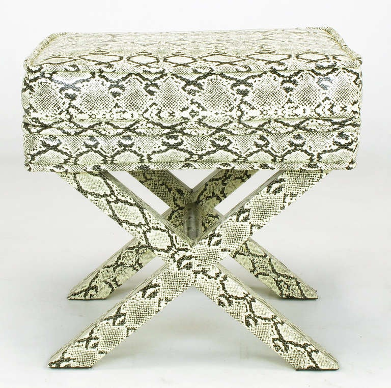 Sleek X base stool covered in faux python skin. Fixed box seat cushion with upper and lower welt. Center stretcher is also fully upholstered.  Evocative of the fully upholstered designs by Billy Baldwin and Karl Springer.